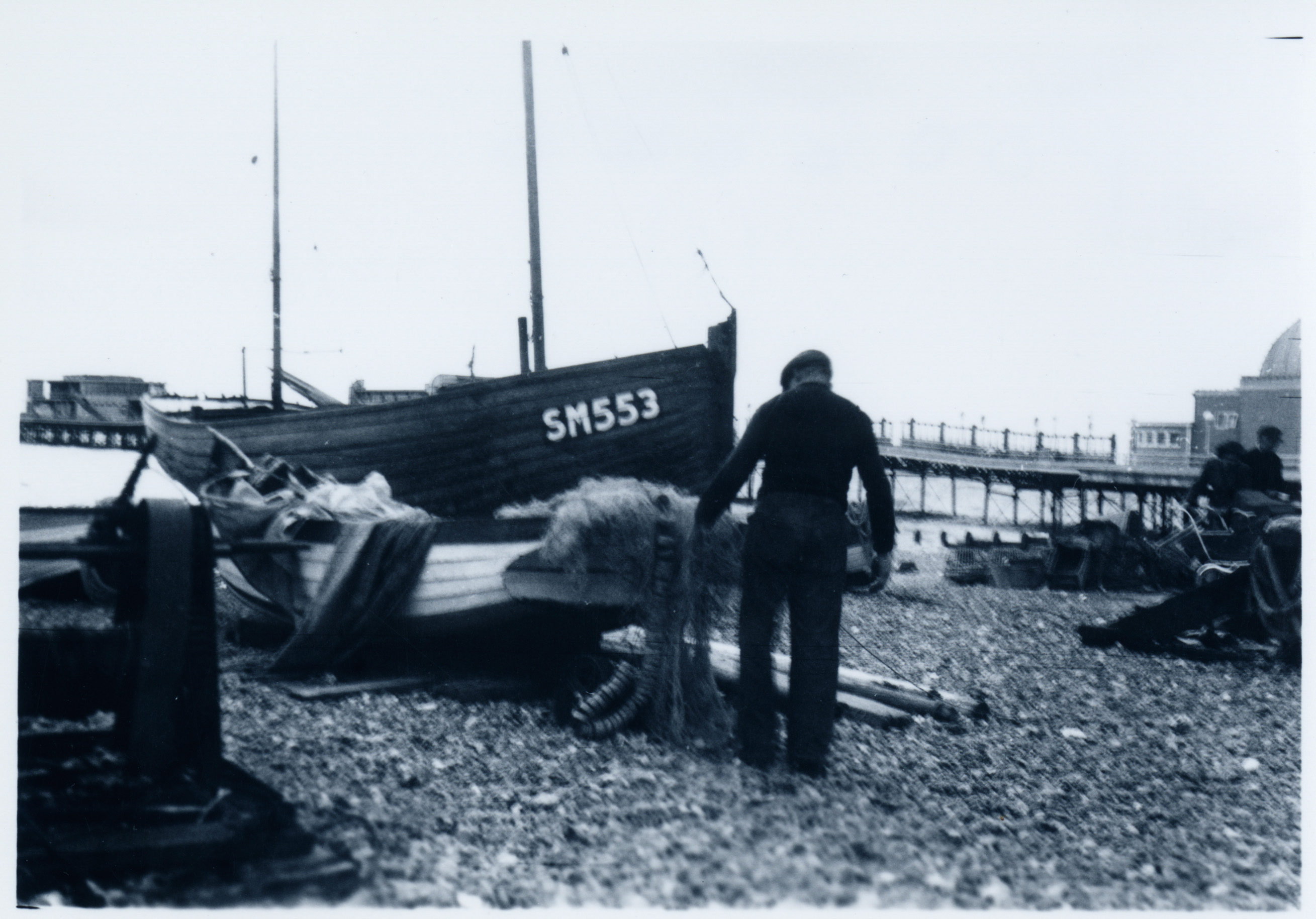 Heritage image of a Fisherman wallking towards his boat on Worthing beach