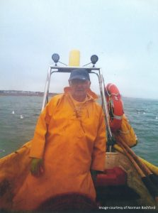 Fisherman Norman BAshford pictured in orange waterproofs aboard his boat while at sea.