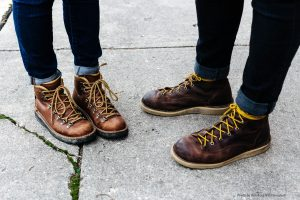Photograph of two pairs of feet, wearing walking shoes, pictured on a pavement